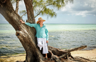 Martha Stewart leaning against a tree on a tropical beach in the Cayman Islands